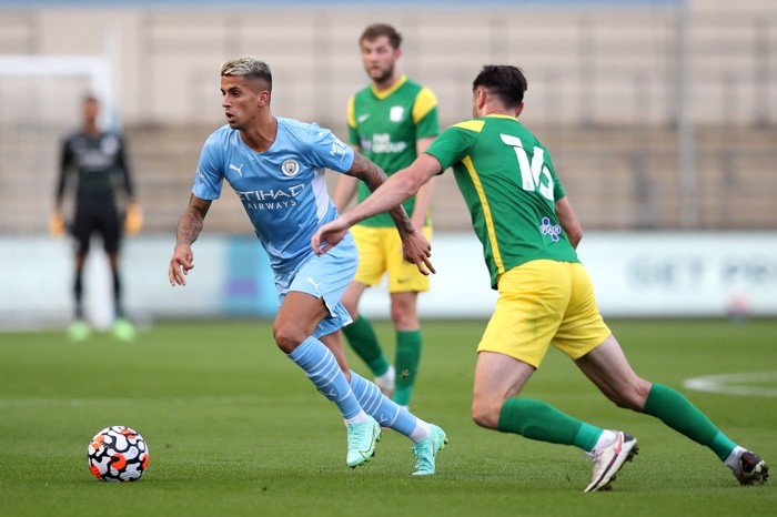 MANCHESTER, ENGLAND - JULY 27: Joao Cancelo of Manchester City controls from Andrew Hughes of Preston North End during a pre-season friendly match between Manchester City and Preston North End at Manchester City Football Academy on July 27, 2021 in Manchester, England. (Photo by Jan Kruger/Getty Images)