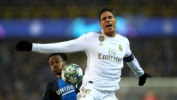 BRUGGE, BELGIUM - DECEMBER 11: Raphael Varane of Real Madrid is challenged by Percy Tau of Club Brugge during the UEFA Champions League group A match between Club Brugge KV and Real Madrid at Jan Breydel Stadium on December 11, 2019 in Brugge, Belgium. (Photo by Dean Mouhtaropoulos/Getty Images)