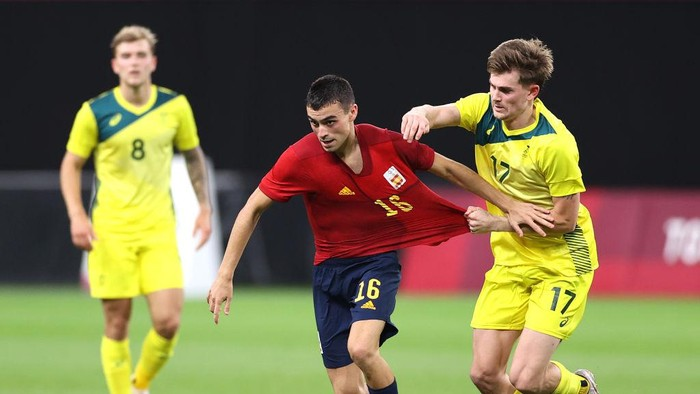 SAPPORO, JAPAN - JULY 25: Pedri Gonzalez #16 of Team Spain is challenged by Connor Metcalfe #17 of Team Australia during the Mens First Round Group C match between Australia and Spain on day two of the Tokyo 2020 Olympic Games at Sapporo Dome on July 25, 2021 in Sapporo, Hokkaido, Japan. (Photo by Masashi Hara/Getty Images)