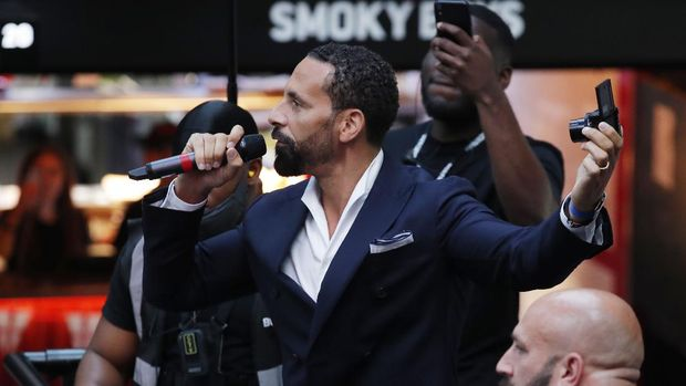 Soccer Football - Euro 2020 - Fans gather for England v Denmark - Boxpark, Wembley, London, Britain - July 7, 2021 Former player Rio Ferdinand talks to the crowd before the match Action Images via Reuters/Andrew Couldridge