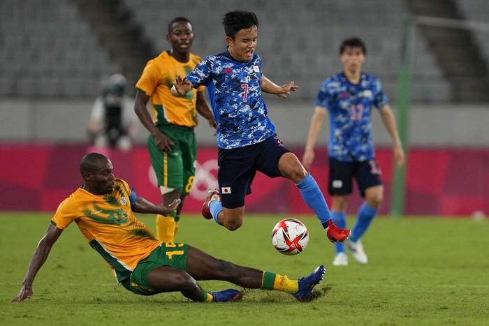 Japan's Takefusa Kubo, leaps over Repo Malepe of South Africa during a men's soccer match at the 2020 Summer Olympics, Thursday, July 22, 2021, in Tokyo, Japan. (AP Photo/Shuji Kajiyama)