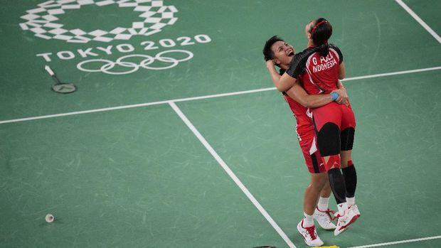 Indonesia's Greysia Polii and Apriyani Rahayu celebrate after defeating South Korea's Lee So-hee and Shin Seung-chan during their women's singles badminton semifinal match at the 2020 Summer Olympics, Saturday, July 31, 2021, in Tokyo, Japan. (AP Photo/Dita Alangkara)