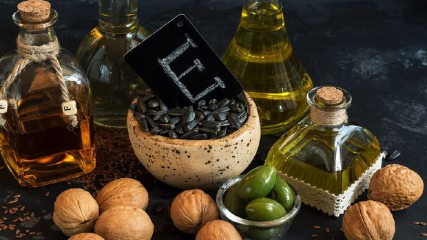 Close-up of products with vitamin E. Olive oil, linseed, walnut and sunflower on a black concrete background.  Selective focus