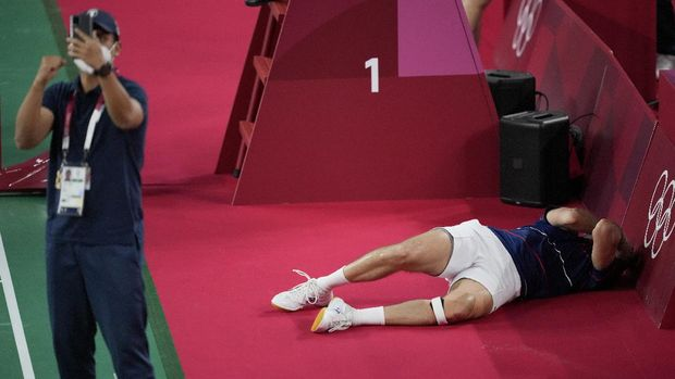 Guatemala's Kevin Cordon, right, reacts after defeating South Korea's Heo Kwang-hee as his coach Muamar Qadafi appears to be using his phone to take photos, during the men's singles badminton quarterfinal match at the 2020 Summer Olympics, Saturday, July 31, 2021, in Tokyo, Japan. (AP Photo/Dita Alangkara)