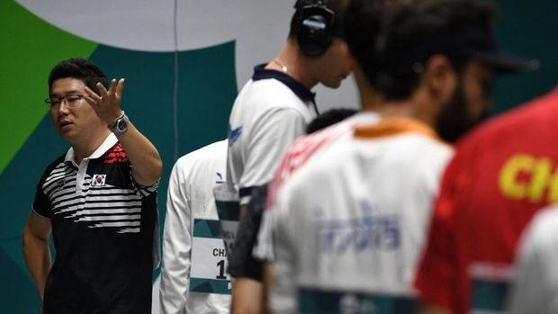 South Korea's Jin Jong-oh (L) argues during the men's 10m air pistol shooting final at the 2018 Asian Games in Palembang on August 21, 2018. (Photo by Mohd RASFAN / AFP)