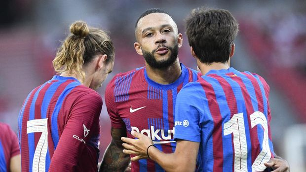 Barcelona's  (L-R) French forward Antoine Griezmann and Dutch forward Memphis Depay congratulate Spanish midfielder Riqui Puig after he scored the 3-0 during a friendly football match VfB Stuttgart v FC Barcelona in Stuttgart, Germany, on July 31, 2021. (Photo by THOMAS KIENZLE / AFP)