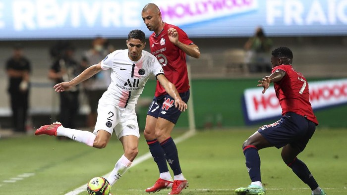 PSGs Achraf Hakimi, left, tries to dribble past Lilles Burak Yilmaz, center, and Lilles Jonathan Bamba during the French Super Cup final soccer match between Lille and Paris Saint-Germain at Bloomfield Stadium in Tel Aviv, Israel, Sunday, Aug. 1, 2021. (AP Photo/Ariel Schalit)
