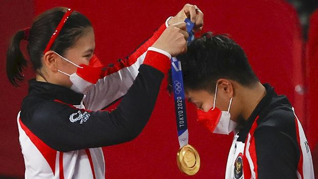 Tokyo 2020 Olympics - Badminton - Women's Doubles - Medal Ceremony - MFS - Musashino Forest Sport Plaza, Tokyo, Japan – August 2, 2021.  Gold medallist Greysia Polii of Indonesia places the medal on teammate Apriyani Rahayu of Indonesia. REUTERS/Hamad I Mohammed