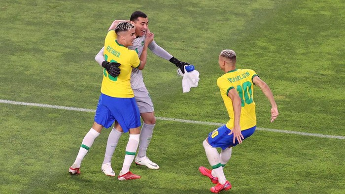 KASHIMA, JAPAN - AUGUST 03: Santos #1, Reinier #19 and Richarlison #10 of Team Brazil celebrates their sides victory in the penalty shoot out after the Mens Football Semi-final match between Mexico and Brazil on day eleven of the Tokyo 2020 Olympic Games at Kashima Stadium on August 03, 2021 in Kashima, Ibaraki, Japan. (Photo by Koki Nagahama/Getty Images)