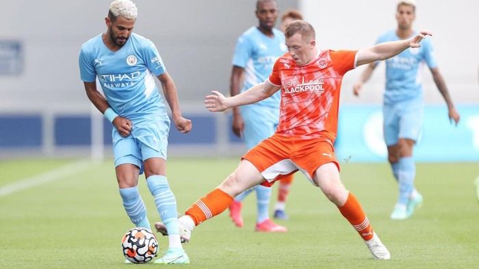 MANCHESTER, ENGLAND - AUGUST 03: Riyad Mahrez of Manchester City is challenged by Shayne Lavery of Blackpool during the Pre-Season Friendly match between Manchester City and Blackpool at Manchester City Football Academy on August 03, 2021 in Manchester, England. (Photo by Lewis Storey/Getty Images)