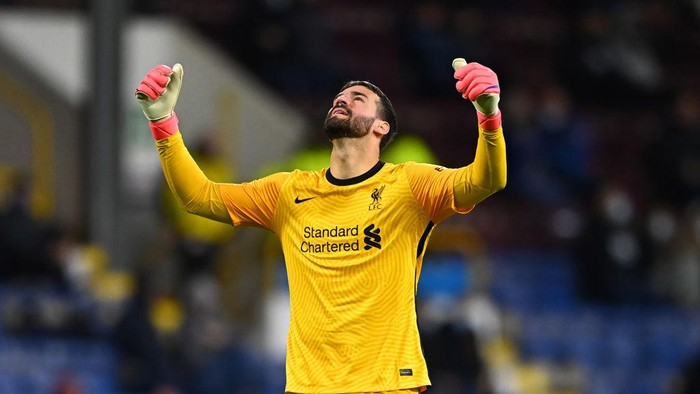 BURNLEY, ENGLAND - MAY 19: Alisson of Liverpool celebrates after their sides third goal scored by Alex Oxlade-Chamberlain (Not pictured) during the Premier League match between Burnley and Liverpool at Turf Moor on May 19, 2021 in Burnley, England. A limited number of fans will be allowed into Premier League stadiums as Coronavirus restrictions begin to ease in the UK. (Photo by Clive Mason/Getty Images)