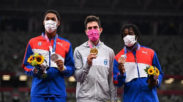 Tokyo 2020 Olympics - Athletics - Men's Long Jump - Medal Ceremony - Olympic Stadium, Tokyo, Japan - August 2, 2021. Gold medallist, Miltiadis Tentoglou of Greece poses on the podium with silver medallist, Juan Miguel Echevarria of Cuba and bronze medallist, Maykel Masso of Cuba as they all wear wearing protective face masks REUTERS/Dylan Martinez