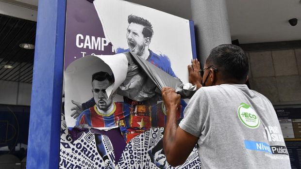 A worker removes posters featuring Barcelona's departing Argentinian forward Lionel Messi at the Camp Nou stadium in Barcelona on August 10, 2021. - France is waiting impatiently for Lionel Messi with supporters gathering outside Paris Saint-Germain's ground hoping to see the Argentine who is expected to join the Qatar-owned club after his exit from Barcelona. (Photo by Pau BARRENA / AFP)