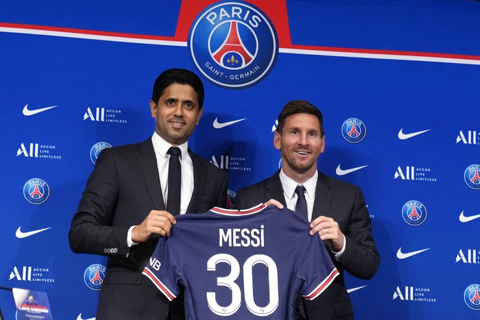 Lionel Messi, right, poses with his jersey with PSG president Nasser Al-Al-Khelaifi during a press conference Wednesday, Aug. 11, 2021 at the Parc des Princes stadium in Paris. Lionel Messi said he's been enjoying his time in Paris