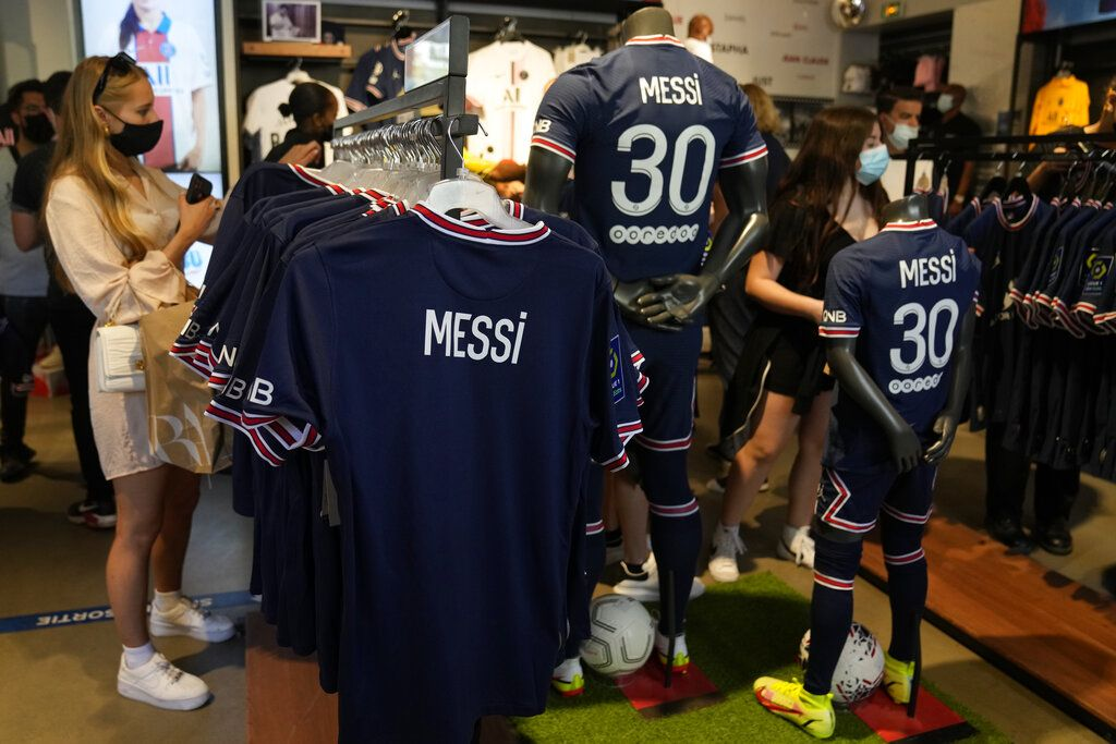 A Parsi Saint-Germain supporter shows a jersey bearing the name of Lionel Messi he just bought as Scarlett Su, right, from New York, smiles outside the official PSG shop, Wednesday, Aug. 11, 2021 in Paris. Lionel Messi is a