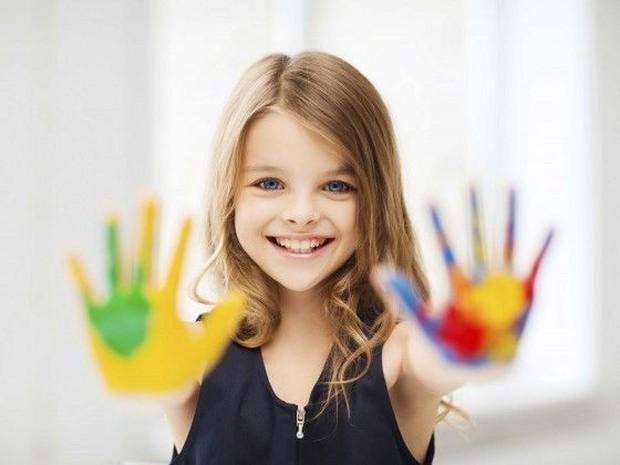 Anak dengan tangan warna warni menatap kamera