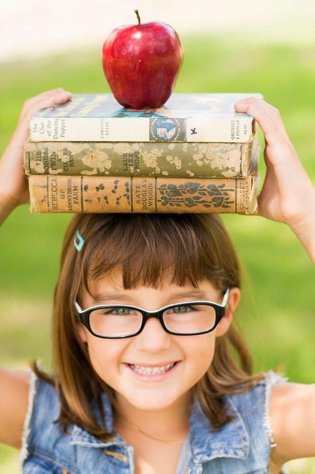 Anak yang mampu menyeimbangkan apel di atas buku yang ia letakan di atas kepalanya