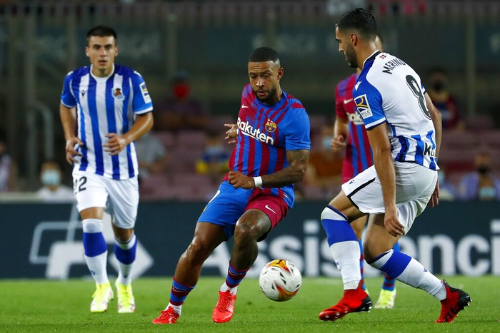 Real Sociedads Mikel Merino, right, vies for the ball with Barcelonas Memphis Depay during a Spanish La Liga soccer match between Barcelona and Real Sociedad at Camp Nou stadium in Barcelona, Spain, Sunday, Aug. 15, 2021. (AP Photo/Joan Monfort)