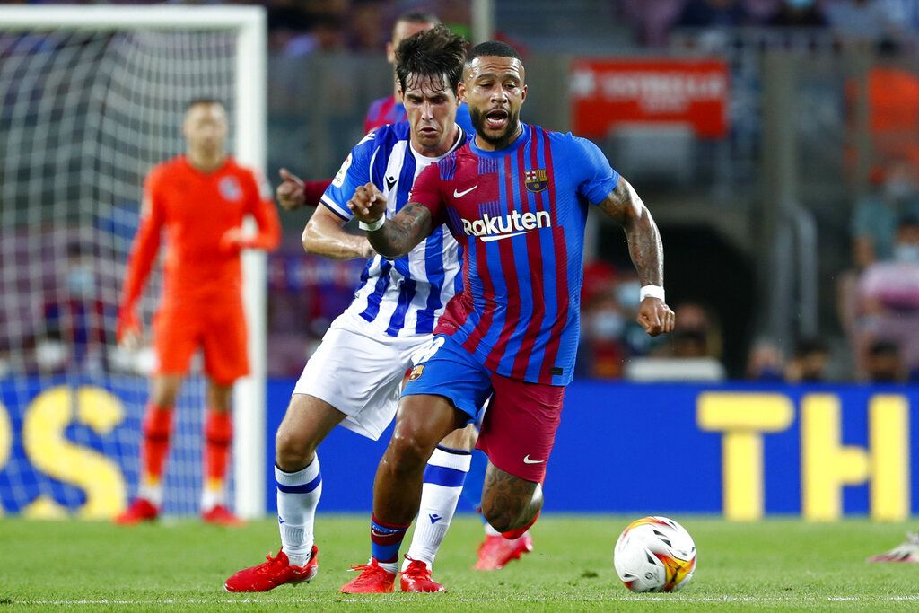 Real Sociedad's Mikel Merino, right, vies for the ball with Barcelona's Memphis Depay during a Spanish La Liga soccer match between Barcelona and Real Sociedad at Camp Nou stadium in Barcelona, Spain, Sunday, Aug. 15, 2021. (AP Photo/Joan Monfort)