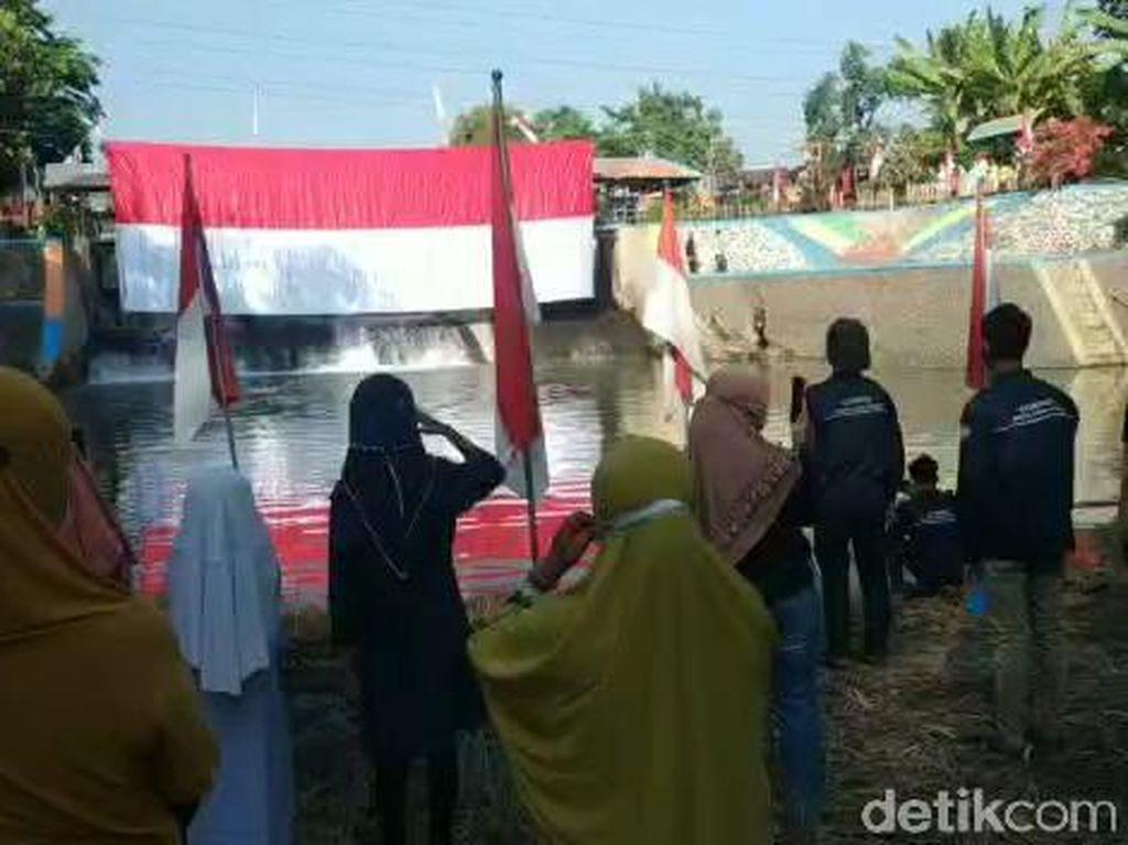 Upacara HUT RI di Pasuruan, Bendera Merah Putih 17 Meter Dikibarkan di Sungai