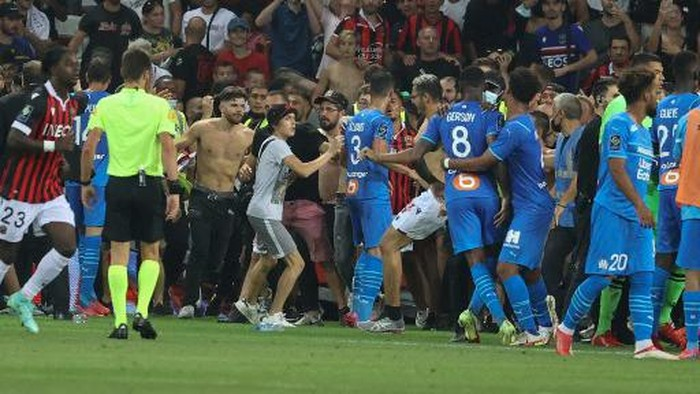 Fans invade the pitch during the French L1 football match between OGC Nice and Olympique de Marseille (OM) at the Allianz Riviera stadium in Nice, southern France on August 22, 2021. - The French Ligue 1 game between Nice and Marseille was halted on August 22, 2021, when fans of the home side invaded the pitch and angrily confronted opposing player Dimitri Payet. An AFP journalist at the game said trouble flared in the 75th minute when Marseille star Payet, who had been targeted by plastic bottles every time he took a corner, lobbed one back into the stands. (Photo by Valery HACHE / AFP)