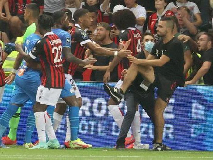 Fans try to invade the pitch during the French L1 football match between OGC Nice and Olympique de Marseille (OM) at the Allianz Riviera stadium in Nice, southern France on August 22, 2021. - The French Ligue 1 game between Nice and Marseille was halted on August 22, 2021, when fans of the home side invaded the pitch and angrily confronted opposing player Dimitri Payet. An AFP journalist at the game said trouble flared in the 75th minute when Marseille star Payet, who had been targeted by plastic bottles every time he took a corner, lobbed one back into the stands. (Photo by Valery HACHE / AFP)