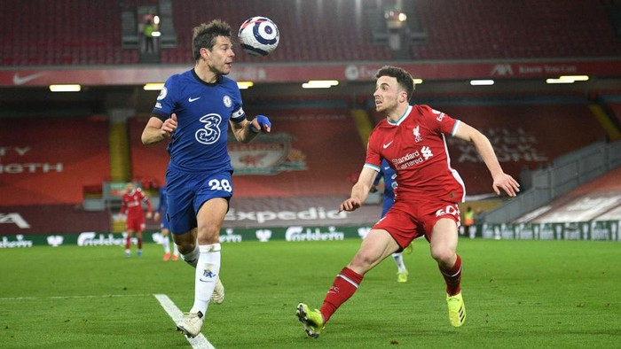 LIVERPOOL, ENGLAND - MARCH 04: Cesar Azpilicueta of Chelsea clears the ball under pressure from Diogo Jota of Liverpool during the Premier League match between Liverpool and Chelsea at Anfield on March 04, 2021 in Liverpool, England. Sporting stadiums around the UK remain under strict restrictions due to the Coronavirus Pandemic as Government social distancing laws prohibit fans inside venues resulting in games being played behind closed doors. (Photo by Oli Scarff - Pool/Getty Images)