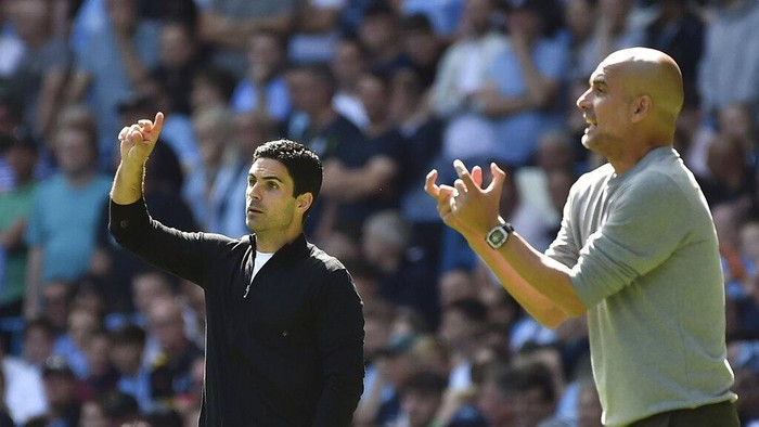 Arsenals manager Mikel Arteta, left, and Manchester Citys head coach Pep Guardiola gesture during the English Premier League soccer match between Manchester City and Arsenal at Etihad stadium in Manchester, England, Saturday, Aug. 28, 2021. (AP Photo/Rui Vieira)