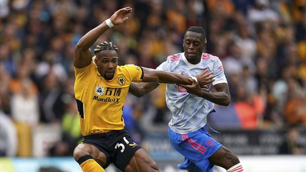 Wolverhampton Wanderers' Adama Traore, left, and Manchester United's Aaron Wan-Bissaka battle for the ball during the English Premier League soccer match between Wolverhampton Wanderers and Manchester United at Molineux Stadium, Wolverhampton, England, Sunday, Aug. 29, 2021. (Nick Potts/PA via AP)