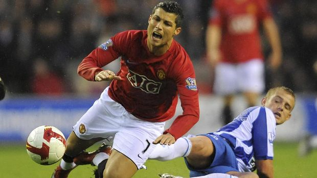 Manchester United's Portugese midfielder Cristiano Ronaldo (L) vies with Wigan Athletic's English midfielder Lee Cattermole during the English Premier league football match at the JJB Stadium in Wigan, north-west, England, on May 13, 2009. AFP PHOTO/ANDREW YATES . FOR EDITORIAL USE ONLY Additional licence required for any commercial/promotional use or use on TV or internet (except identical online version of newspaper) of Premier League/Football League photos. Tel DataCo +44 207 2981656. Do not alter/modify photo. (Photo by ANDREW YATES / AFP)