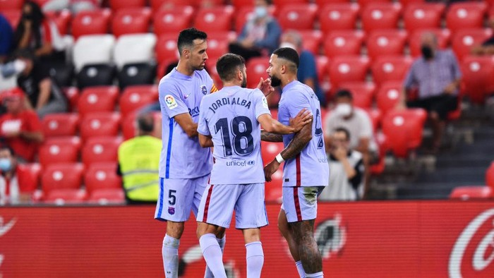 BILBAO, SPAIN - AUGUST 21: Memphis Depay of FC Barcelona celebrates with teammates Jordi Alba and Sergio Busquets after scoring his sides first goal during the LaLiga Santander match between Athletic Club and FC Barcelona at San Mames Stadium on August 21, 2021 in Bilbao, Spain. (Photo by Juan Manuel Serrano Arce/Getty Images)
