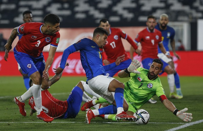 Brazils Bruno Guimaraes, center, kicks the ball in an attempt to score as Chiles goalkeeper Claudio Bravo defends during a qualifying soccer match for the FIFA World Cup Qatar 2022 at Monumental Stadium in Santiago, Chile, Thursday, Sept. 2, 2021. (Claudio Reyes/Pool via AP)