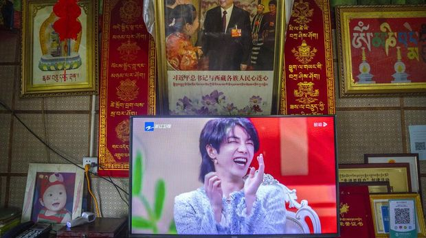 FILE - In this June 4, 2021, file photo, a television shows a broadcast of a Chinese talk show program as it sits beneath a photo of Chinese President Xi Jinping in a home converted into a tourist homestay in Zhaxigang village near Nyingchi in western China's Tibet Autonomous Region. China's government banned effeminate men on TV and told broadcasters Thursday, Sept. 2, 2021 to promote