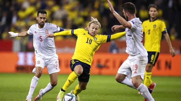Spains Sergio Busquets, left, and Aymeric Laporte, right, fight for the ball with Swedens Emil Forsberg, center, during the World Cup 2022, group B soccer match between Sweden and Spain at Friends Arena, in Stockholm, Sweden, Thursday, Sept. 2, 2021. (Nils Petter Nilsson/TT via AP)