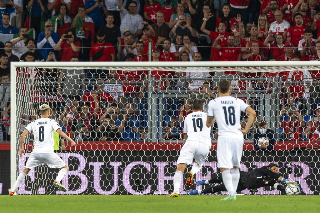 Switzerland goalkeeper Yann Sommer, right, catches the penalty kick of Italy's Jorginho, left, during the World Cup 2022 Group C qualifying soccer match between Switzerland and Italy at the St. Jakob-Park stadium in Basel, Switzerland, on Sunday, Sept. 5, 2021. (Jean-Christophe Bott/Keystone via AP)