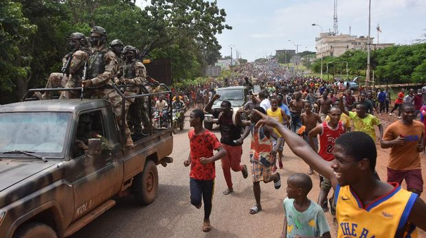 People celebrate in the streets with members of Guinea's armed forces after the arrest of Guinea's president, Alpha Conde, in a coup d'etat in Conakry, September 5, 2021. - Guinean special forces seized power in a coup on September 5, arresting the president and imposing an indefinite curfew in the poor west African country.