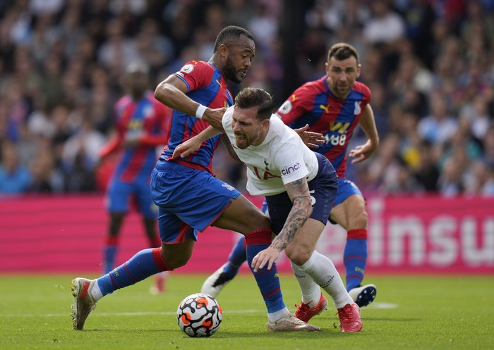 Crystal Palaces Jordan Ayew, left, and Tottenhams Pierre-Emile Hojbjerg challenge for the ball during the English Premier League soccer match between Tottenham Hotspur and Crystal Palace at the Selhurst Park stadium in London, Saturday, Sept. 11, 2021. (AP Photo/Alastair Grant)