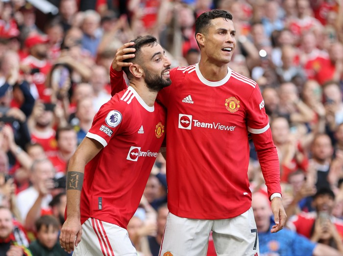 MANCHESTER, ENGLAND - SEPTEMBER 11: Bruno Fernandes of Manchester United celebrates with Cristiano Ronaldo after scoring their side's third goal during the Premier League match between Manchester United and Newcastle United at Old Trafford on September 11, 2021 in Manchester, England. (Photo by Clive Brunskill/Getty Images)