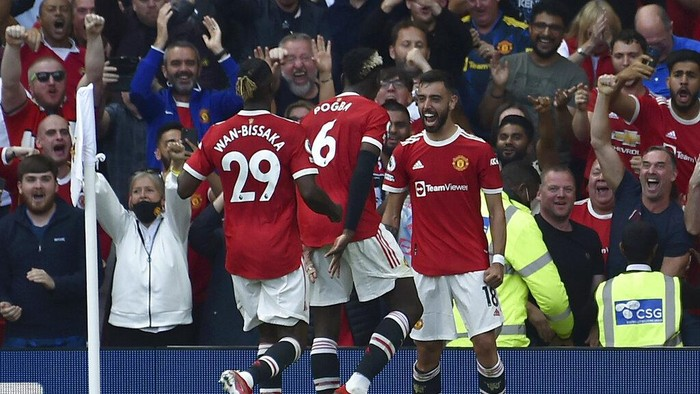 Manchester Uniteds Bruno Fernandes, right, celebrates after scoring his sides third goal during the English Premier League soccer match between Manchester United and Newcastle United at Old Trafford stadium in Manchester, England, Saturday, Sept. 11, 2021. (AP Photo/Rui Vieira)