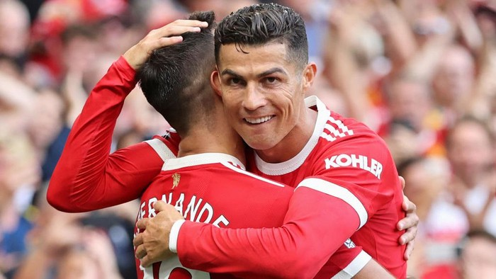 MANCHESTER, ENGLAND - SEPTEMBER 11: Bruno Fernandes of Manchester United celebrates with Cristiano Ronaldo after scoring their sides third goal during the Premier League match between Manchester United and Newcastle United at Old Trafford on September 11, 2021 in Manchester, England. (Photo by Clive Brunskill/Getty Images)