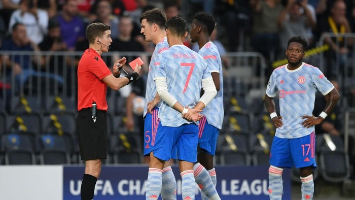 BERN, SWITZERLAND - SEPTEMBER 14: Harry Maguire of Manchester United talks with Referee Francois Letexier after Aaron Wan-Bissaka of Manchester United (not pictured) is shown a red card during the UEFA Champions League group F match between BSC Young Boys and Manchester United at Stadion Wankdorf on September 14, 2021 in Bern, Switzerland. (Photo by Matthias Hangst/Getty Images)