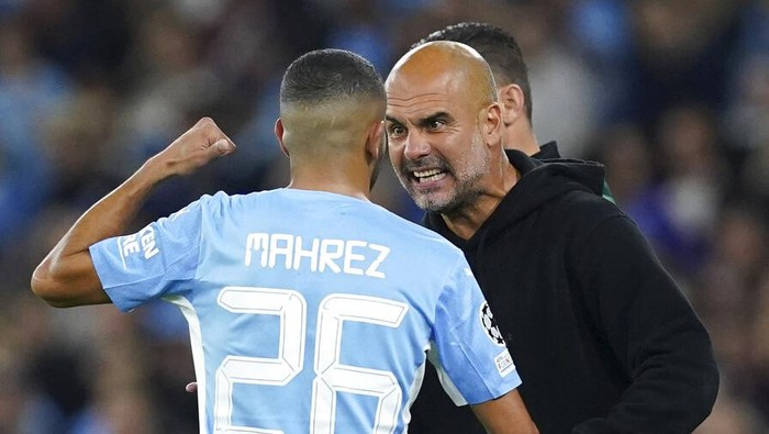 Manchester Citys Riyad Mahrez speaks with manager Pep Guardiola on the touchline during the Champions League Group A soccer match between Manchester City and RB Leipzig at the Etihad Stadium, Manchester, England, Wednesday Sept. 15, 2021. (Martin Rickett/PA via AP)