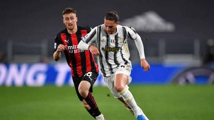TURIN, ITALY - MAY 09: Adrien Rabiot of Juventus runs with the ball whilst under pressure from Alexis Saelemaekers of A.C. Milan during the Serie A match between Juventus  and AC Milan at  on May 09, 2021 in Turin, Italy. Sporting stadiums around Italy remain under strict restrictions due to the Coronavirus Pandemic as Government social distancing laws prohibit fans inside venues resulting in games being played behind closed doors. (Photo by Valerio Pennicino/Getty Images)