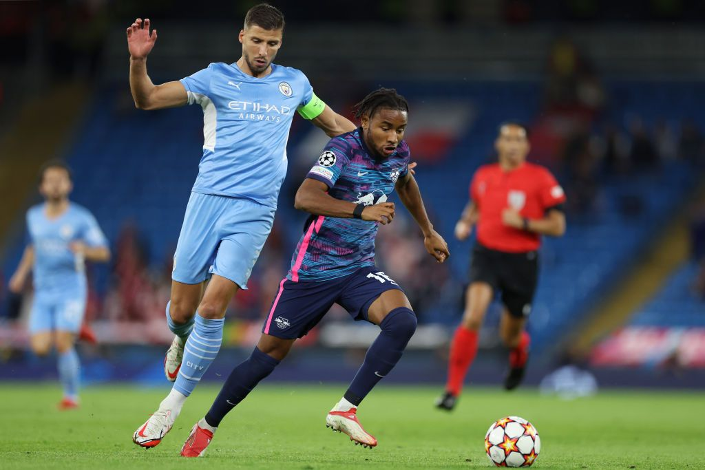 MANCHESTER, ENGLAND - SEPTEMBER 15: Christopher Nkunku of RB Leipzig is challenged by Ruben Dias of Manchester City during the UEFA Champions League group A match between Manchester City and RB Leipzig at Etihad Stadium on September 15, 2021 in Manchester, England. (Photo by Richard Heathcote/Getty Images)
