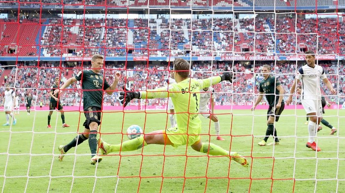 MUNICH, GERMANY - SEPTEMBER 18: Joshua Kimmich (L) of FC Bayern Muenchen scores his second goal against goalkeeper Manuel Riemann of Bochum during the Bundesliga match between FC Bayern München and VfL Bochum at Allianz Arena on September 18, 2021 in Munich, Germany. (Photo by Alexander Hassenstein/Getty Images)