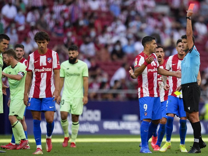 Atletico Madrids Joao Felix, left, is shown the red card during a Spanish La Liga soccer match between Atletico Madrid and Athletic Bilbao at Wanda Metropolitano stadium in Madrid, Spain, Saturday, Sept. 18, 2021. (AP Photo/Manu Fernandez)