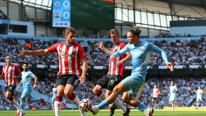 MANCHESTER, ENGLAND - SEPTEMBER 18: Jack Grealish of Manchester City passes the ball under pressure from Jack Stephens and James Ward-Prowse of Southampton during the Premier League match between Manchester City and Southampton at Etihad Stadium on September 18, 2021 in Manchester, England. (Photo by Alex Livesey/Getty Images)