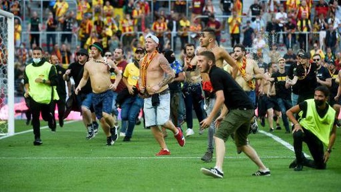 Lens supporters invade the pitch during the French L1 football match between RC Lens (RCL) and Lille (LOSC) at Stade Bollaert-Delelis in Lens, northern France, on September 18, 2021. (Photo by FRANCOIS LO PRESTI / AFP)