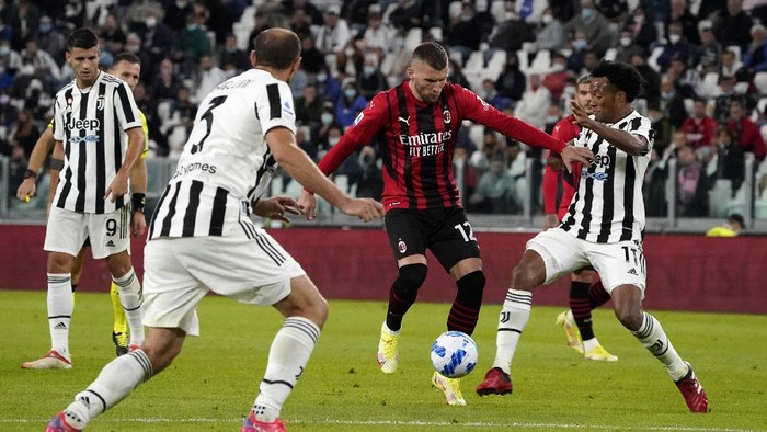 TURIN, ITALY - SEPTEMBER 19: Ante Rebic of AC Milan is challenged by Juan Cuadrado of Juventus during the Serie A match between Juventus and AC Milan at the Allianz Stadium in Turin, Italy on September 19, 2021 in Turin, Italy. (Photo by Pier Marco Tacca/Getty Images)
