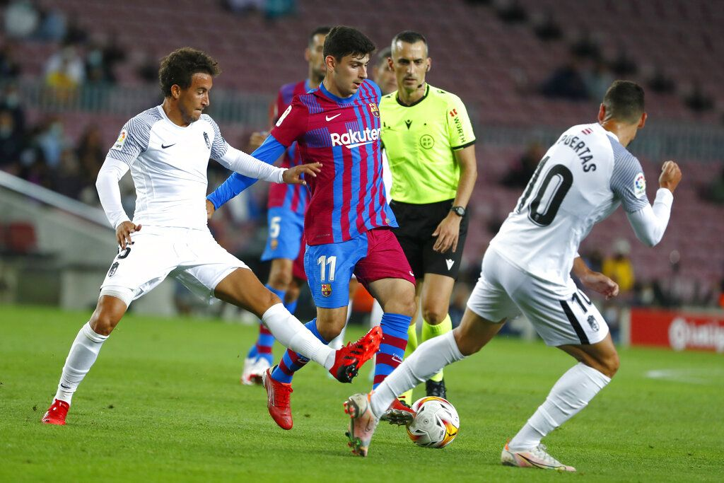 Granada's Luis Milla, left, challenges for the ball with Barcelona's Yusuf Demir during the Spanish La Liga soccer match between Barcelona and Granada, at the Camp Nou stadium in Barcelona, Spain, Monday, Sept. 20, 2021. (AP Photo/Joan Monfort)